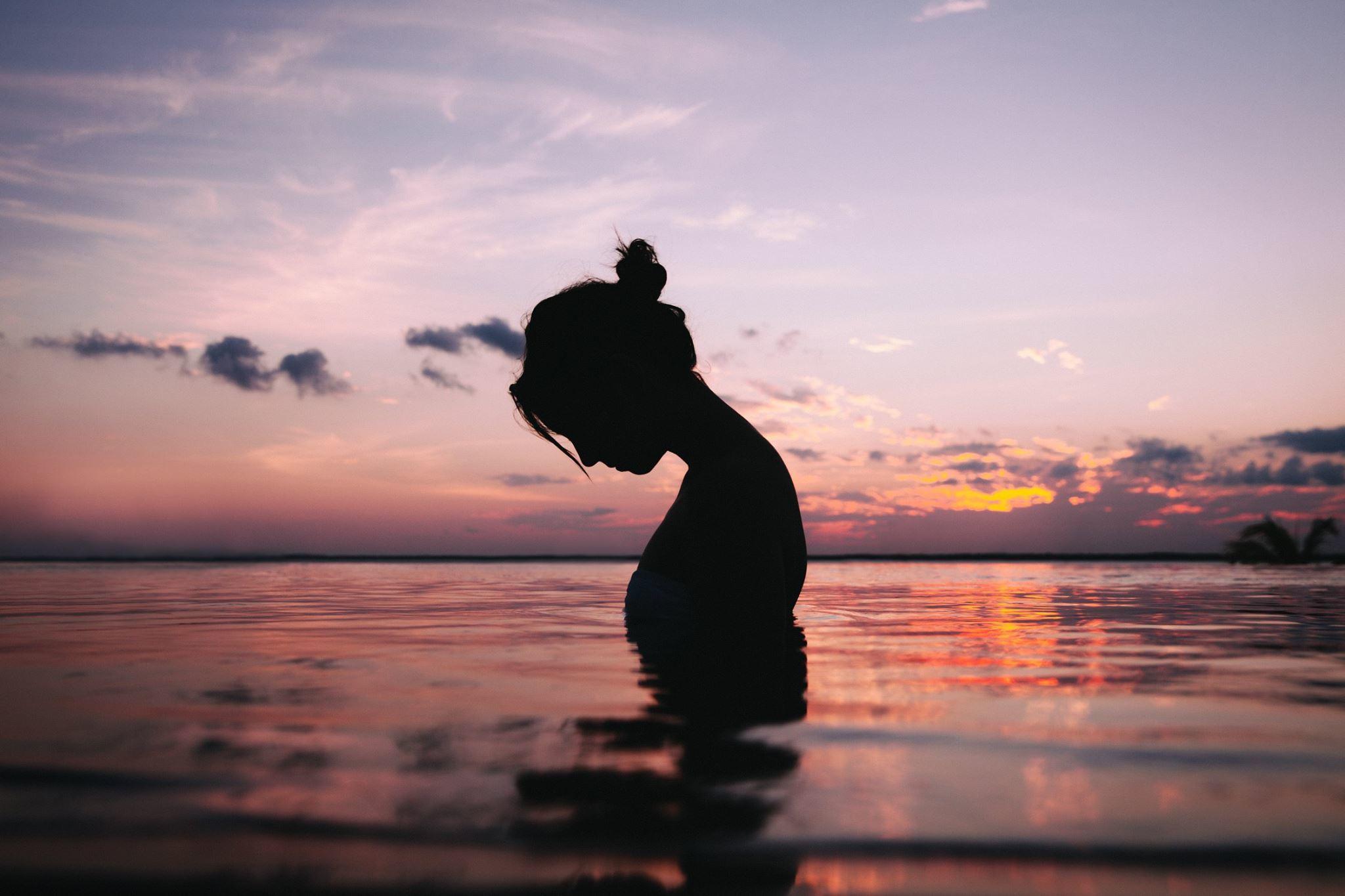 Hình nền buồn cô gái đứng dưới nước cúi đầu