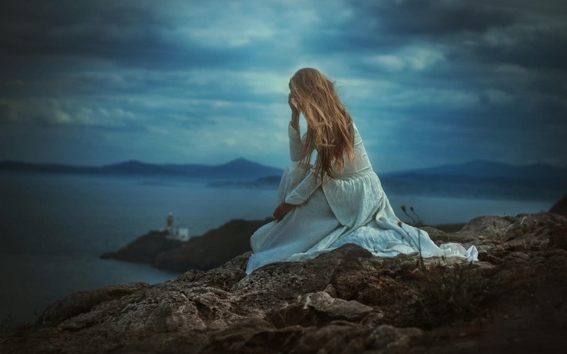 Hình nền buồn cô gái ngồi bên bờ biển