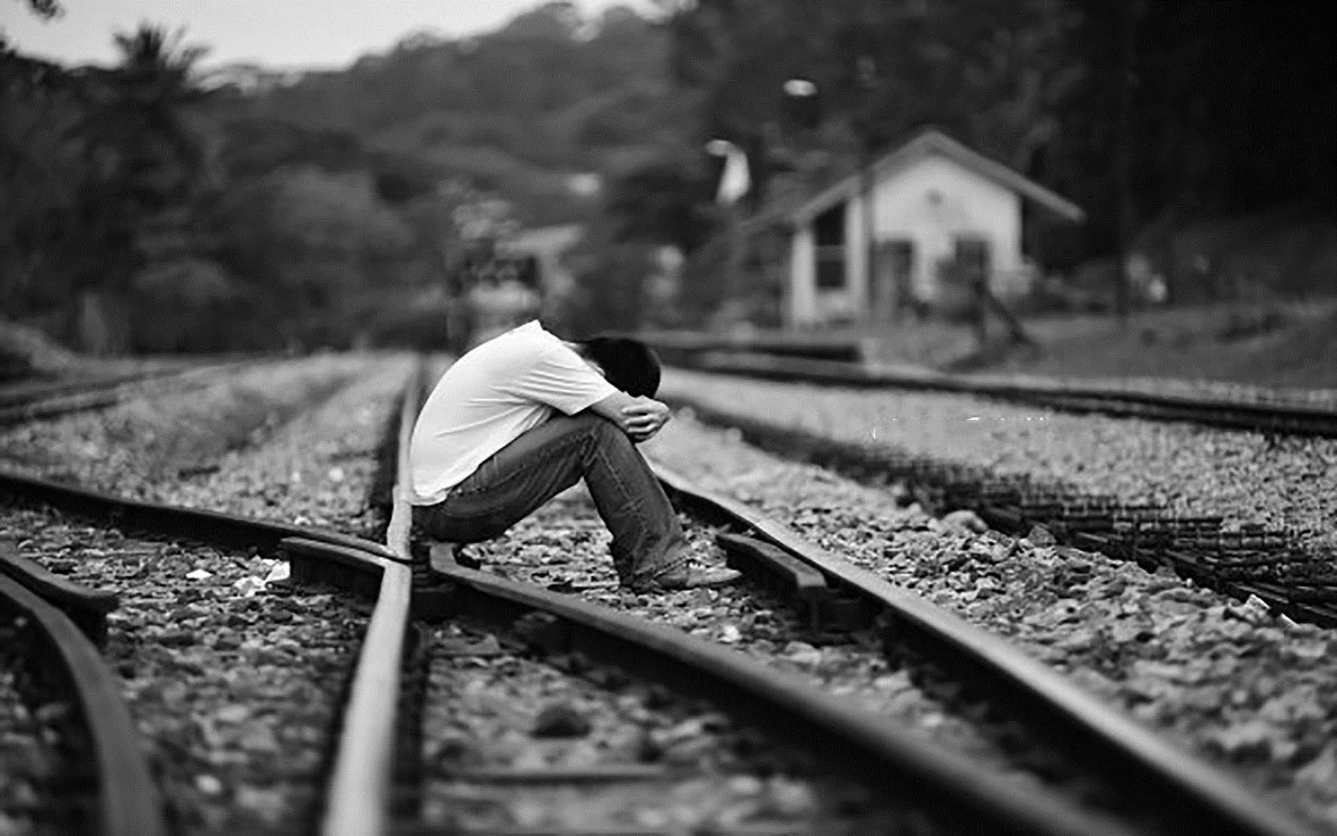 Hình nền chàng trai ngồi khóc trên đường ray trông rất buồn